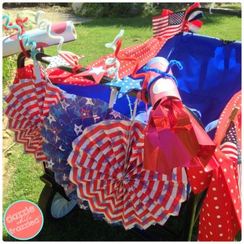 Hang red, white and blue patriotic paper fans on back of utility wagon for kids neighborhood 4th of July bike parade.