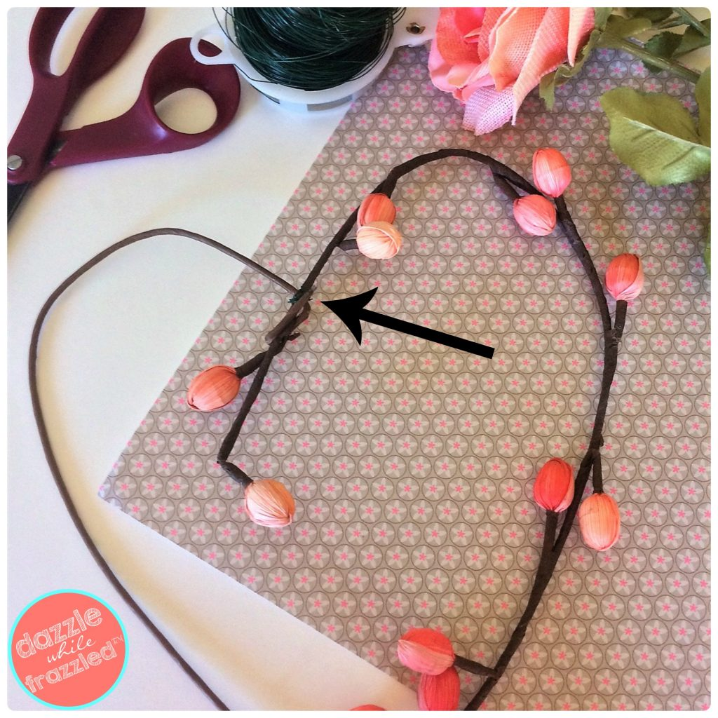 Use floral wire to secure a flower stem into a heart shape for a DIY heart flower wreath