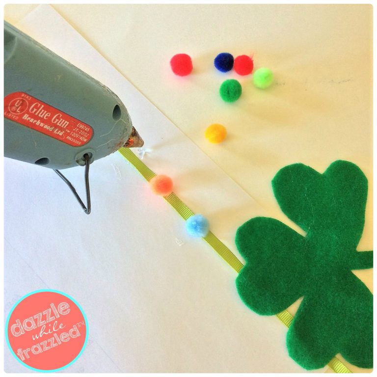 "Hot glue gun rainbow craft pom poms to a DIY ""lucky"" St. Patrick's Day garland for Irish home decor"