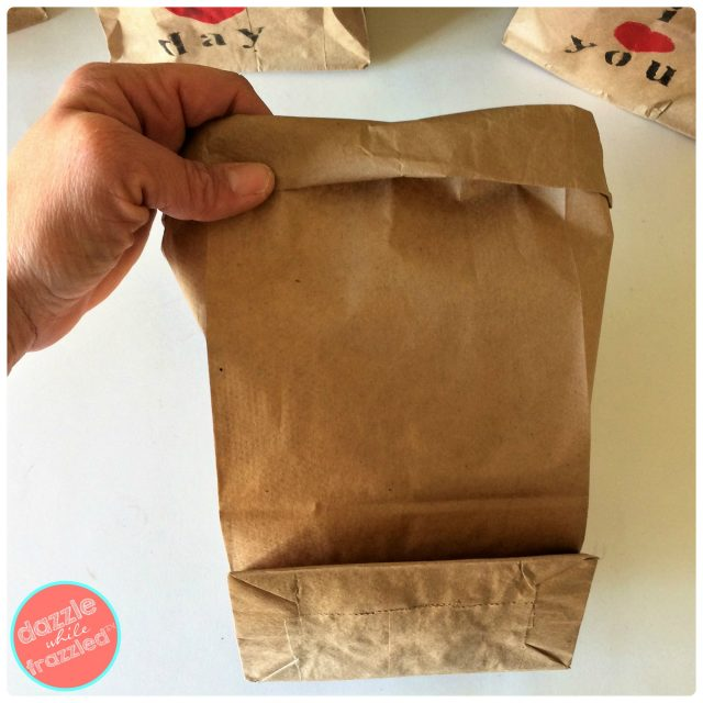 Open brown paper lunch bag and roll down opening for DIY paper gift bag for potted plants.