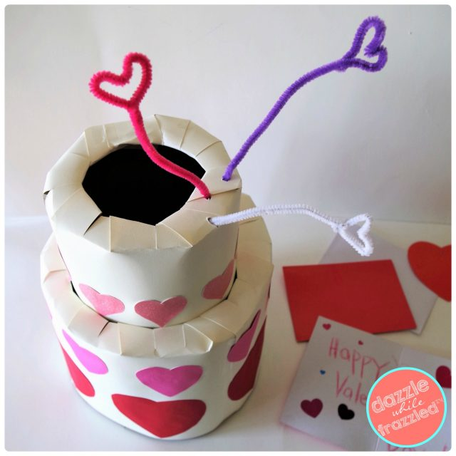 Add pipe cleaners to cardboard Valentine's Day tiered cake box card holder for kids.