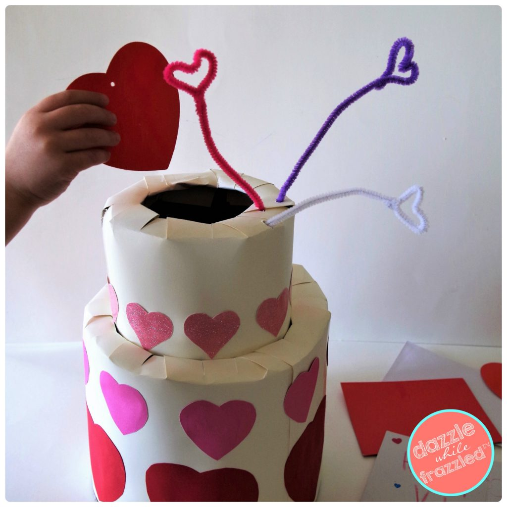 DIY Valentine's Day card holder for kids classroom Valentine's card exchange in shape of cardboard tiered wedding cake.