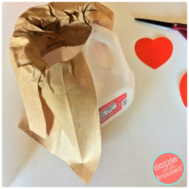 Cut down sides of brown paper lunch bag and cover plastic milk jug to make kids volcano Valentine's Day card box holder.