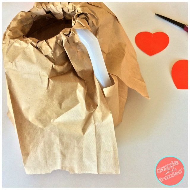 Cover plastic milk jug with brown paper lunch bags to make kids volcano Valentine's Day card holder for classrom Valentine exchange.