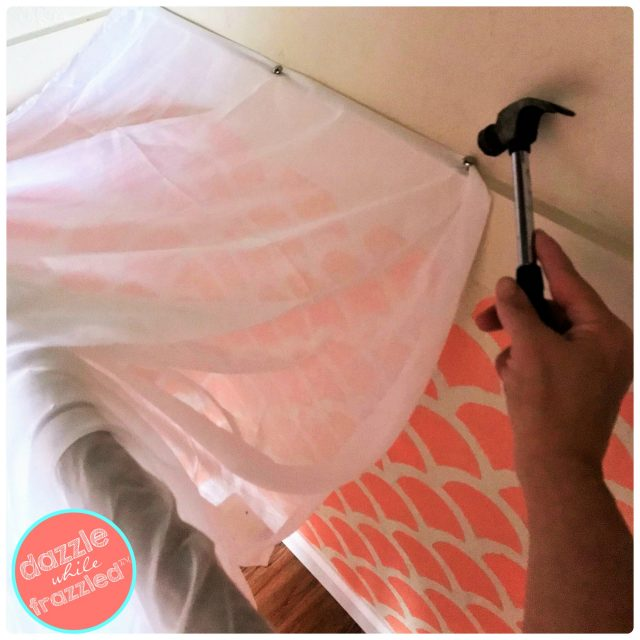 Make a DIY reading nook using sheer fabric and upholstery tacks to create a canopy roof for kids closet reading corner.